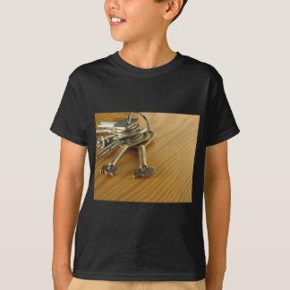 Bündel abgenutzte Hausschlüssel auf hölzerner T-Shirt