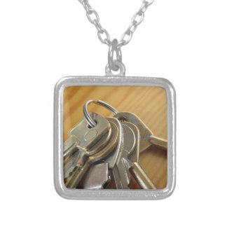 Bündel abgenutzte Hausschlüssel auf hölzerner Versilberte Kette