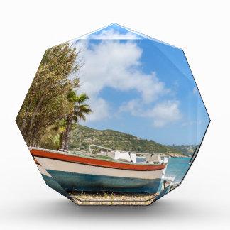 Buntes Boot, das auf griechischem Strand liegt Auszeichnung