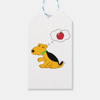 Cartoon-Entwurfairedale-Hund, der an einen Apple Geschenkanhänger