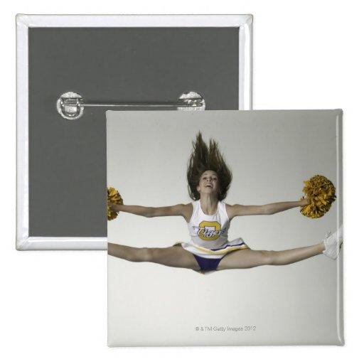 Cheerleader, die Spalten in der mittleren Luft tut Anstecknadelbuttons