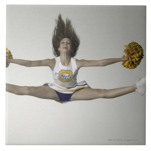 Cheerleader, die Spalten in der mittleren Luft tut Keramikfliesen