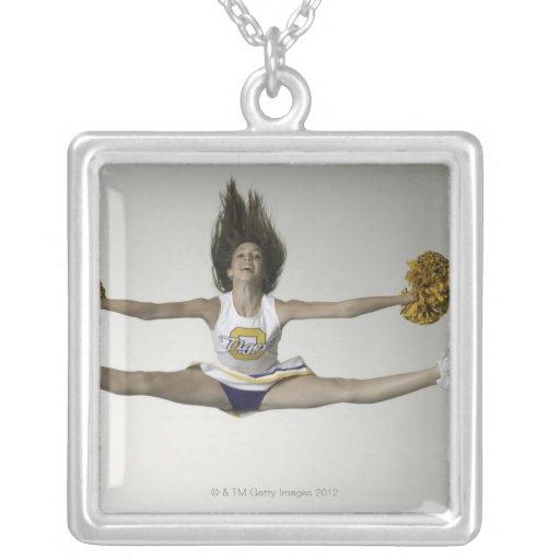 Cheerleader, die Spalten in der mittleren Luft tut Amuletten