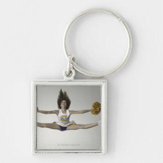 Cheerleader, die Spalten in der mittleren Luft tut Silberfarbener Quadratischer Schlüsselanhänger