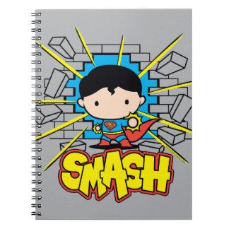 Chibi Supermann, der durch Backsteinmauer Spiral Notizblock