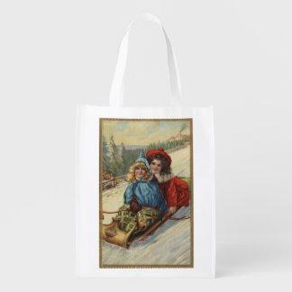 ChristmasTwo kleine Mädchen Sledding Einkaufstaschen