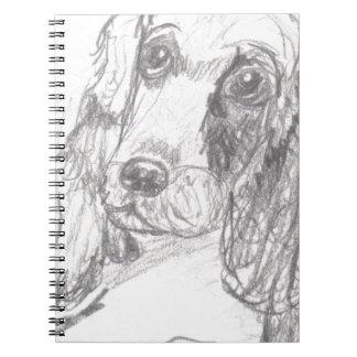 Cockerspanielhund, der Eliana zeichnet Notizblock
