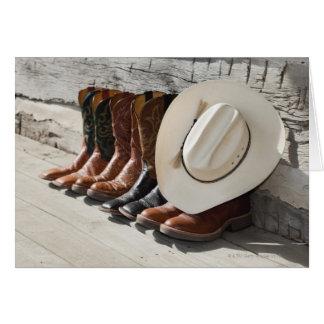 Cowboyhut auf Reihe der Cowboystiefel außerhalb Karte
