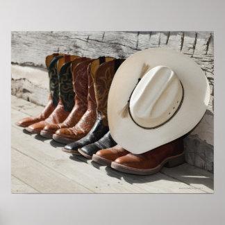 Cowboyhut auf Reihe der Cowboystiefel außerhalb Poster