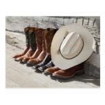 Cowboyhut auf Reihe der Cowboystiefel außerhalb Postkarten