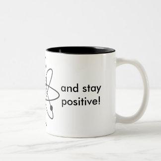 Denken Sie wie ein Proton und bleiben Sie positiv! Zweifarbige Tasse