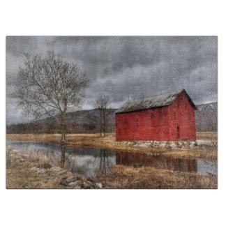 Die rote Scheune, die im Teich-Schneidebrett sich Schneidebrett