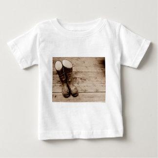 Die schlammigen Gummistiefel eines Bauern Baby T-shirt