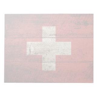 Die Schweiz-Flagge auf altem hölzernem Korn Notizblock