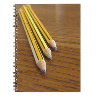 Drei benutzte Bleistifte auf hölzerner Tabelle Notizblock