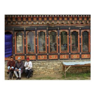 Drei Männer sitzen auf einer Bank beim Postkarte