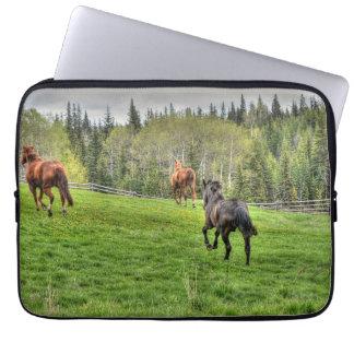Drei Pferde, die auf frisches Gras in einer Koppel Laptop Sleeve