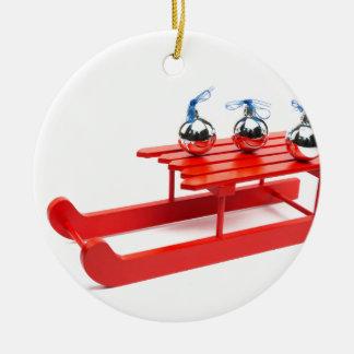 Drei silberne Weihnachtsbälle auf rotem Schlitten Rundes Keramik Ornament