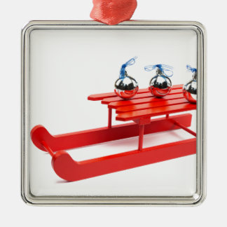Drei silberne Weihnachtsbälle auf rotem Schlitten Silbernes Ornament