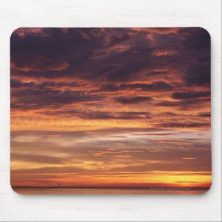 Dunkle Wolken in Orange gestreiftem Himmel Mousepad