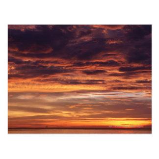 Dunkle Wolken in Orange gestreiftem Himmel Postkarte
