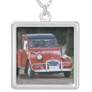 Ein altes rotes Auto Citroen 2CV mit einer Halskette Mit Quadratischem Anhänger
