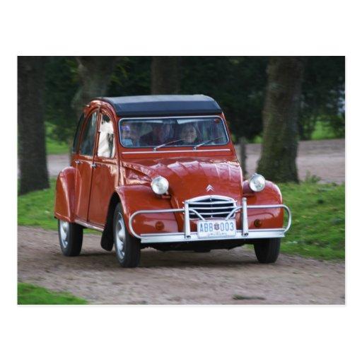Ein altes rotes Auto Citroen 2CV mit einer lächeln Postkarten