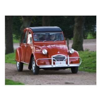 Ein altes rotes Auto Citroen 2CV mit einer Postkarte