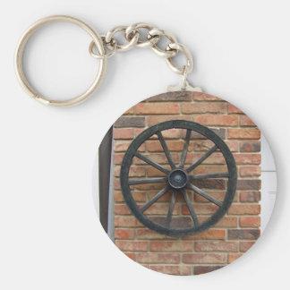 Ein altes Wagenrad auf einer Backsteinmauer Standard Runder Schlüsselanhänger