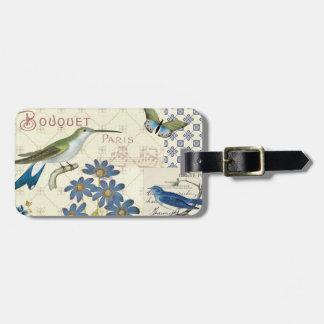 Ein Blumenstrauß der blauen Blumen, der Vögel und Kofferanhänger