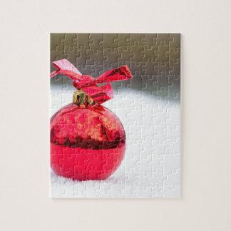 Ein glänzender roter Weihnachtsball draußen im Puzzle