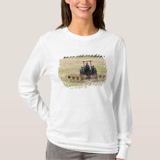Ein junger Junge, der ein Traktorernten fährt T-Shirt
