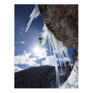 Ein männlicher Snowboarder springt weg von einem Postkarte