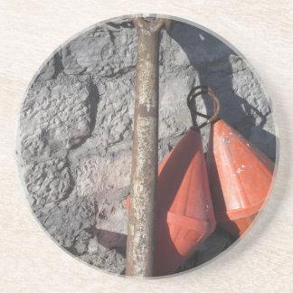 Ein rostiger Anker und eine orange konische Boje Sandstein Untersetzer