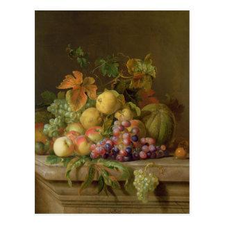 Ein Stillleben der Melonen, der Trauben und der Postkarte