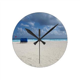 Ein Strand-Stuhl erwartet Runde Wanduhr