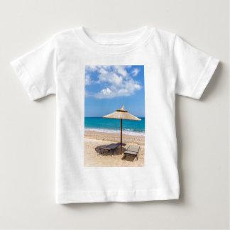 Ein Strandschirm und sunloungers nähern sich Ozean Baby T-shirt