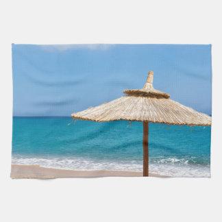 Ein Strandschirm und sunloungers nähern sich Ozean Küchentuch