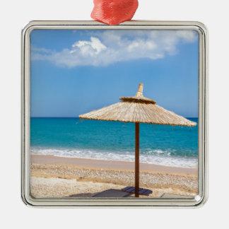 Ein Strandschirm und sunloungers nähern sich Ozean Quadratisches Silberfarbenes Ornament