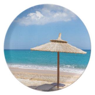 Ein Strandschirm und sunloungers nähern sich Ozean Teller