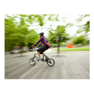 Eine Frau, die ein faltendes Fahrrad verwendet, um Postkarte
