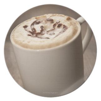 Eine Tasse Cappuccinokaffee überstieg mit Teller