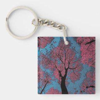 einem blauen Himmel u. einem rosa Baum oben Schlüsselanhänger