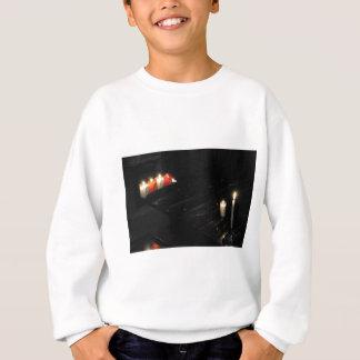 Einige religiöse Kerzen auf einer schwarzen Sweatshirt