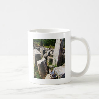 Entzückende Streukatze, die in den Ruinen von Kaffeetasse
