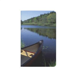 Erholungen eines Kanus auf dem Ufer von wenigem Taschennotizbuch