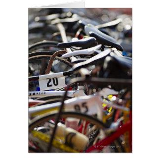 Fahrräder auf dem Gestell an einem Triathlon laufe Grußkarte