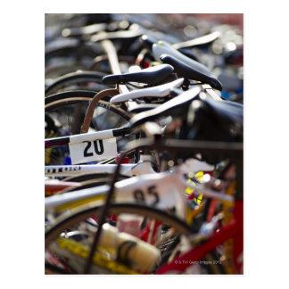 Fahrräder auf dem Gestell an einem Triathlon laufe Postkarte