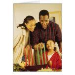 Familie, die das Kinara für Kwanzaa beleuchtet Grußkarte