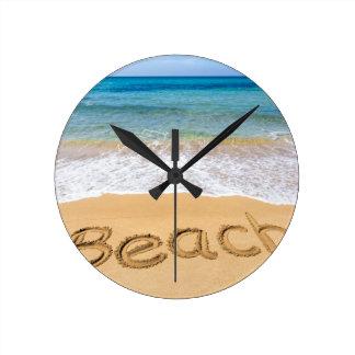 Fassen Sie den Strand ab, der in Sand in Runde Wanduhr
